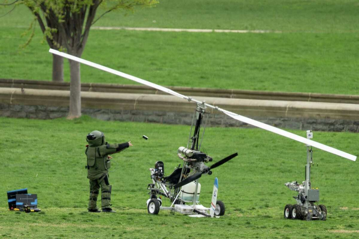 A member of a bomb squad pulls something off of a small helicopter and throws it after a man landed on the West Lawn of the Capitol in Washington, Wednesday, April 15, 2015. Police arrested a man who steered his tiny, one-person helicopter onto the West Lawn of the U.S. Capitol Wednesday, astonishing spring tourists and prompting a temporary lockdown of the Capitol Visitor Center. Capitol Police didn't immediately identify the pilot or comment on his motive, but a Florida postal carrier named Doug Hughes took responsibility for the stunt on a website where he said he was delivering letters to all 535 members of Congress in order to draw attention to campaign finance corruption.