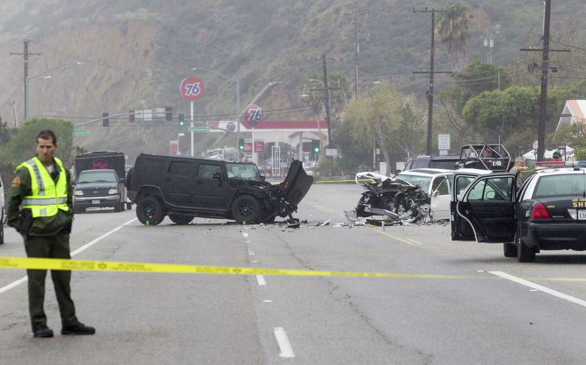 """FILE - In this Saturday, Feb. 7, 2015 file photo, Los Angeles County Sheriff's deputy guards the scene of a collision involving three vehicles in Malibu, Calif. Sheriff's investigators plan to recommend prosecutors file a vehicular manslaughter charge against Caitlyn Jenner for her role in the fatal car crash on the Pacific Coast Highway in Malibu last February. Los Angeles County Sheriff's Department spokeswoman Nicole Nishida says investigators found that Jenner was driving """"unsafe for the prevailing road conditions"""" because her SUV rear-ended a Lexus, pushing it into oncoming traffic."""