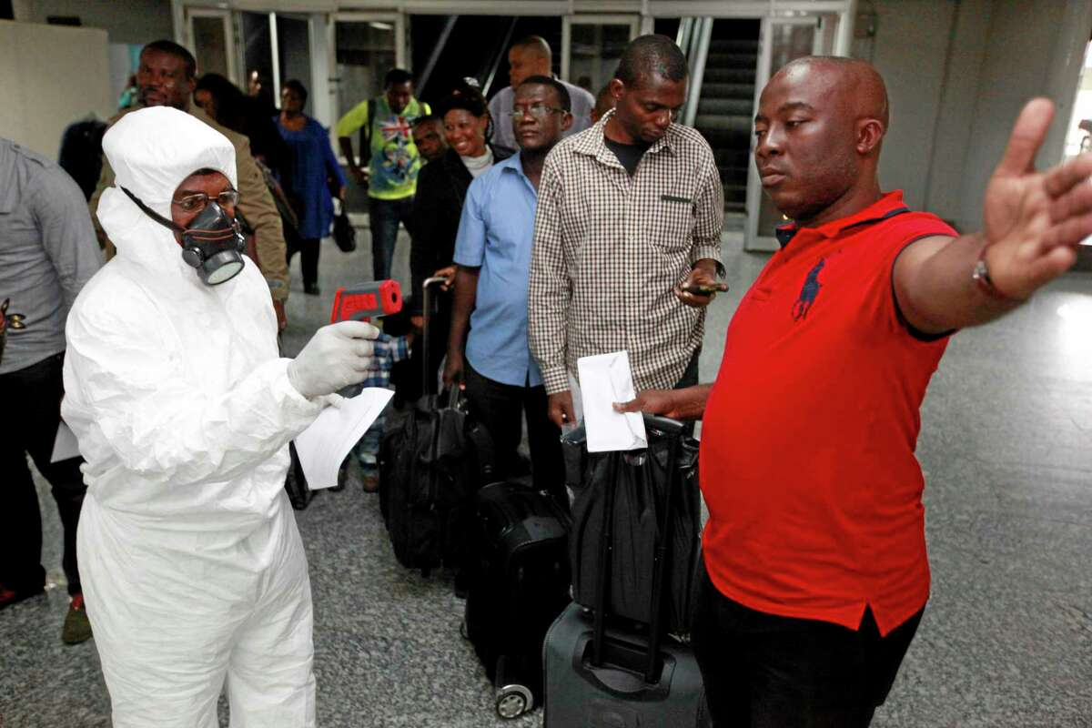 FILE - In this Wednesday, Aug. 6, 2014 file photo, a Nigerian port health official uses a thermometer on a passengers at the arrivals hall of Murtala Muhammed International Airport in Lagos, Nigeria. Two new cases of Ebola have emerged in Nigeria and, in an alarming development, they are outside the group of caregivers who treated an airline passenger who arrived with Ebola and died, Health Minister Onyebuchi Chukwu said Friday, Aug. 22, 2014. (AP Photo/Sunday Alamba, File)