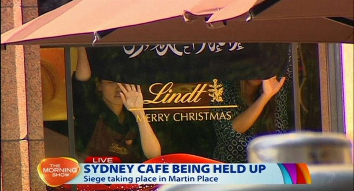 This image taken from video shows people holding up what appeared to be a black flag with white Arabic writing on it, inside a cafe in Sydney, Australia Monday, Dec. 15, 2014. An apparent hostage situation was unfolding inside the chocolate shop and cafe in Australia's largest city on Monday, where several people could be seen through a window with their hands held in the air.