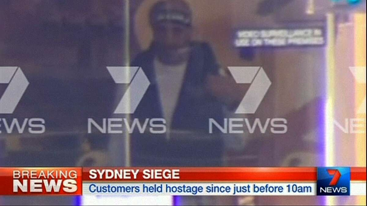 This image taken from video shows a man believed to be a gunman inside a cafe in Sydney, Australia Monday, Dec. 15, 2014. An apparent hostage situation was unfolding inside the chocolate shop and cafe in Australia's largest city on Monday, where several people could be seen through a window with their hands held in the air.