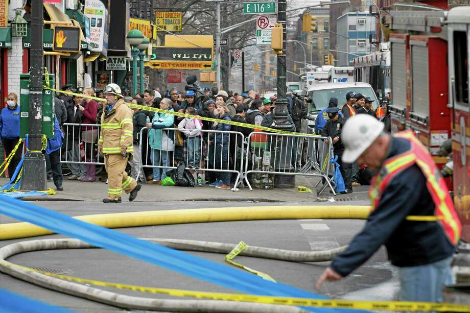Firefighters respond to an explosion and building collapse in the East Harlem neighborhood of New York, Wednesday, March 12, 2014. The explosion leveled an apartment building, and sent flames and billowing black smoke above the skyline. (AP Photo/John Minchillo) Photo: AP / FR170537 AP