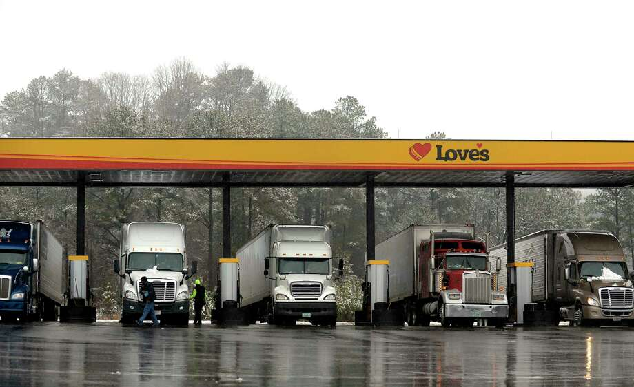 In this Feb. 11, 2014 photo, truck drivers stop at a gas station in Emerson, Ga., north of metro Atlanta, to fill up their tractor trailer rigs. A new government rule being announced by the Federal Motor Carrier Safety Administration on Thursday, Dec. 10, 2015, requires an estimated 3 million commercial truck and bus drivers to electronically record their hours behind the wheel in an effort to enforce regulations to prevent fatigue. Photo: AP Photo/David Tulis, File  / FR170493 AP