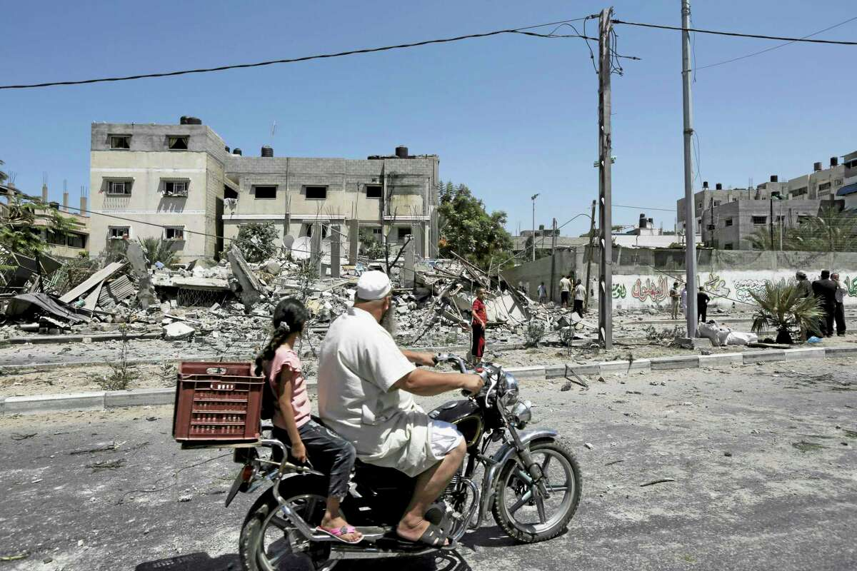 Palestinians on a motorcycle look at an area damaged after an Israeli airstrike as others inspect the rubble of their family house in Gaza City in the northern Gaza Strip, Saturday, Aug. 23, 2014. (AP Photo/Adel Hana)