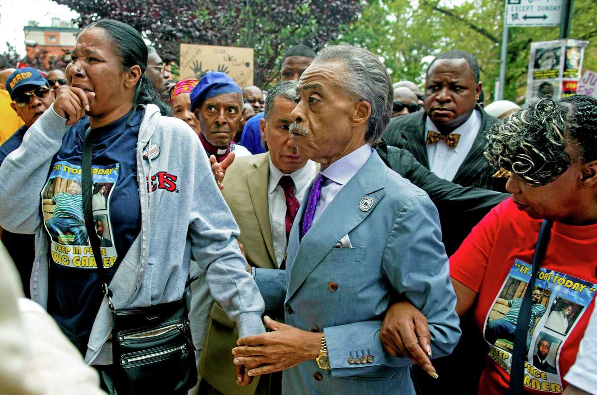 Esaw Garner, left, arrives at the spot where her husband Eric Garner died with The Rev. Al Sharpton, center, and Eric Garner's mother Gwen Carr, right, at the start of a march and rally in the Staten Island borough of New York, Saturday, Aug. 23, 2014. The city medical examiner ruled that Eric Garner, 43, died as a result of a police chokehold during an attempted arrest. (AP Photo/Craig Ruttle)