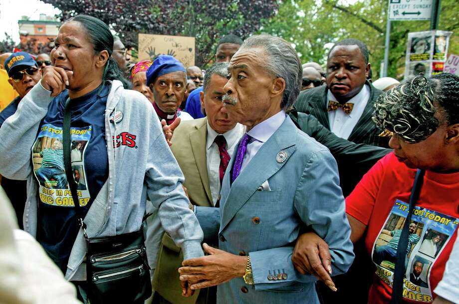Esaw Garner, left, arrives at the spot where her husband Eric Garner died with The Rev. Al Sharpton, center, and Eric Garner's mother Gwen Carr, right, at the start of a march and rally in the Staten Island borough of New York, Saturday, Aug. 23, 2014. The city medical examiner ruled that Eric Garner, 43, died as a result of a police chokehold during an attempted arrest. (AP Photo/Craig Ruttle) Photo: AP / FR61802 AP