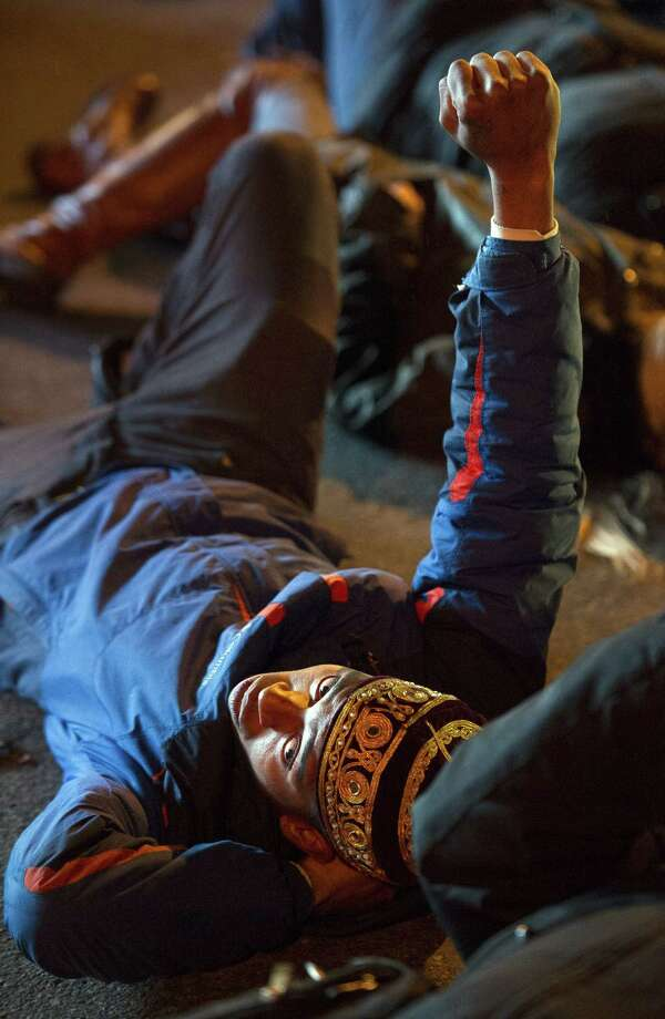 """Deon Johnson, 19, of Washington, DC, raises his fist as he and others take part in a four and-a-half minute """"die-in"""" while blocking an intersection in downtown,Washington, Friday, Dec. 5, 2014, during a demonstration against the deaths of two unarmed black men at the hands of white police officers in New York City and Ferguson, Mo.  (AP Photo/Cliff Owen) Photo: AP / FR170079 AP"""