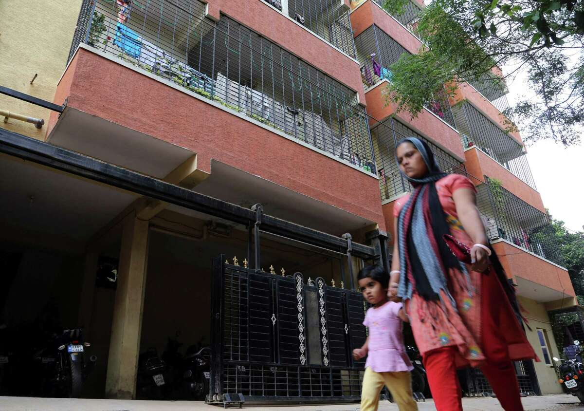 An Indian woman and a child walk past a building housing the apartment where Mehdi Masroor Biswas lives in Bangalore, India, Saturday, Dec. 13, 2014. Police in southern India said Saturday that they have arrested Biswas, a 24-year-old engineer, who has admitted to running a popular pro-Islamic State group Twitter account, but added that he appears to have no direct links to the militant group. (AP Photo/Aijaz Rahi)