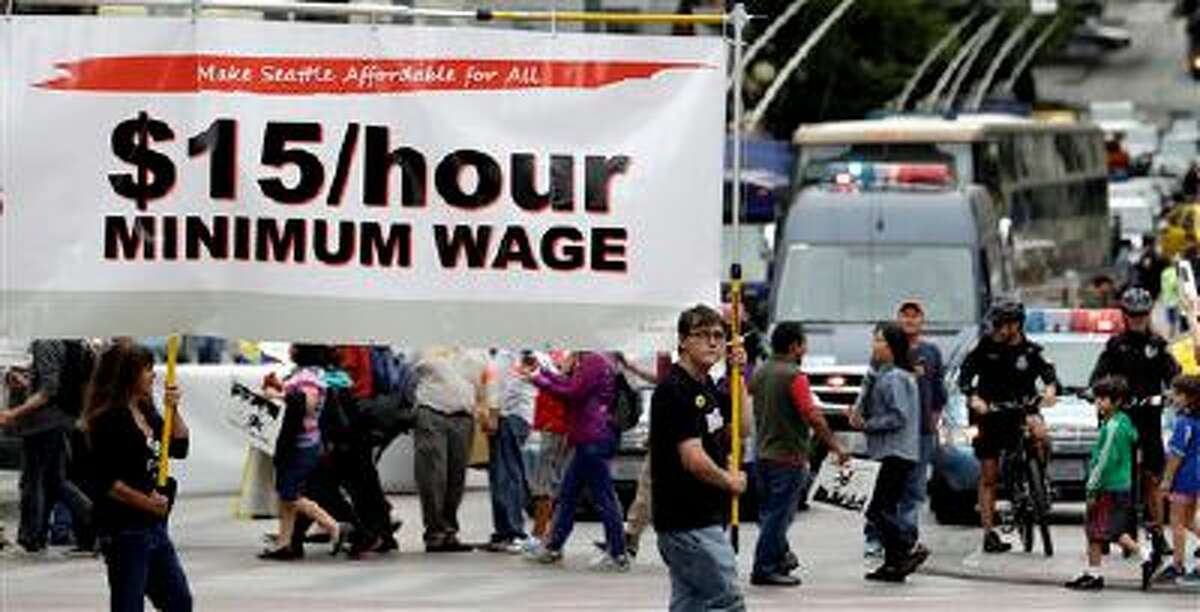 In this Aug. 1, 2013 photo, demonstrators protesting what they say are low wages and improper treatment for fast-food workers march in downtown Seattle. Washington already has the nation?s highest state minimum wage at $9.19 an hour. Now, there?s a push in Seattle, at least, to make it $15. That would mean fast food workers, retail clerks, baristas and other minimum wage workers would get what protesters demanded when they shut down a handful of city restaurants in May and others demonstrated nationwide in July. (AP Photo/Elaine Thompson)