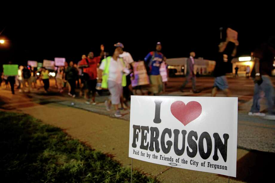 Protesters march Thursday, Aug. 21, 2014, in Ferguson, Mo. Protesters again gathered Thursday evening, walking in laps near the spot where Michael Brown was shot. Some were in organized groups, such as clergy members. More signs reflected calls by protesters to remove the white prosecutor from the case.  (AP Photo/Jeff Roberson) Photo: AP / AP
