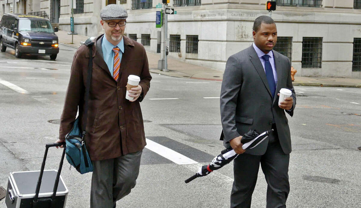 In this Dec. 2, 2015 file photo, Baltimore City police Officer William Porter, right, one of six Baltimore police officers charged with the death of Freddie Gray, walks to the courthouse with one of his attorneys in Baltimore. Porter faces manslaughter, assault, misconduct in office and reckless endangerment charges.