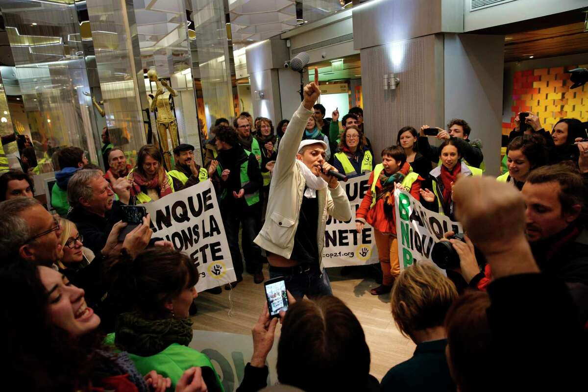 """Activists from the NGO """"Non violent action COP21"""" sing and dance during a concert in a BNP Paribas bank they have occupied, in Paris on Dec. 9, 2015. The protest is one of many activist actions linked to the COP21, the United Nations Climate Change Conference."""