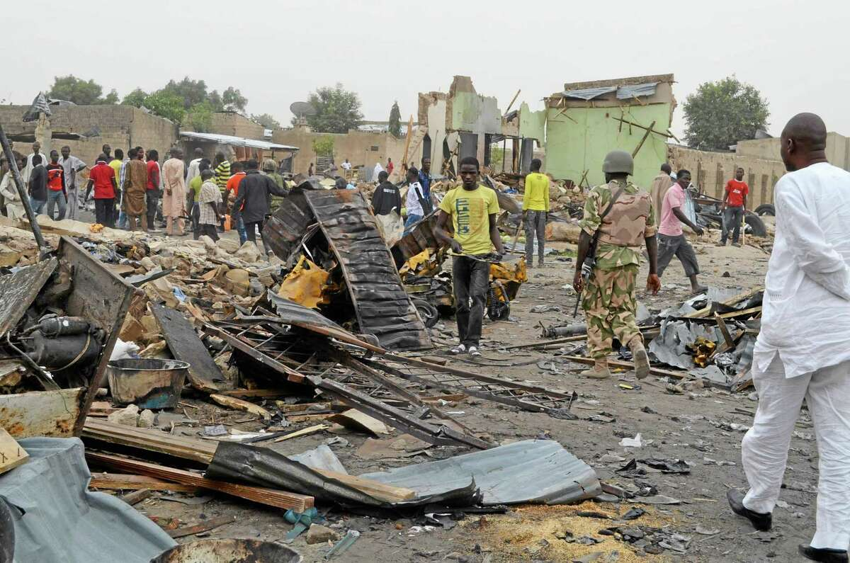 People gather at the site of a twin car bomb explosion in Maiduguri, Nigeria, Sunday, March 2, 2014. Twin car bomb blasts at a bustling marketplace killed at least 51 people in Maiduguri, the northeast Nigerian city that is the birthplace of Nigeria's Islamic extremist terrorist group, a Red Cross official said Sunday. (AP Photo/Jossy Ola )