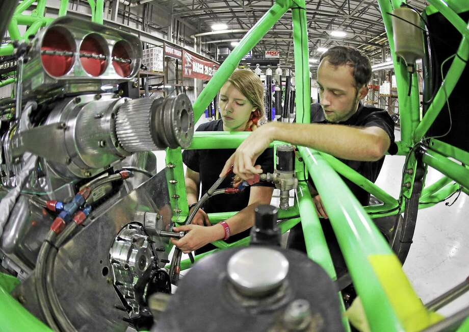 Lauren Dorgan, left, and Cory McGee work on an engine of a monster truck at Feld Entertainment in Ellenton, Fla. Photo: Chris O'Meara — The Associated Press  / AP