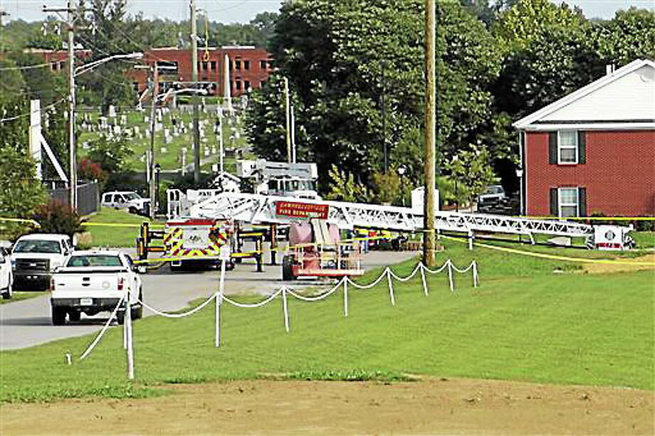 A Campbellsville Fire Department truck with the ladder extended remained at the scene where two firefighters were injured during an ice bucket challenge during a fundraiser for ALS on Thursday, Aug. 21, 2014, in Campbellsville, Ky. Officials say the ladder got too close to a power line and electricity traveled to the ladder, electrocuting the firefighters. (AP Photo/Dylan Lovan) Photo: AP