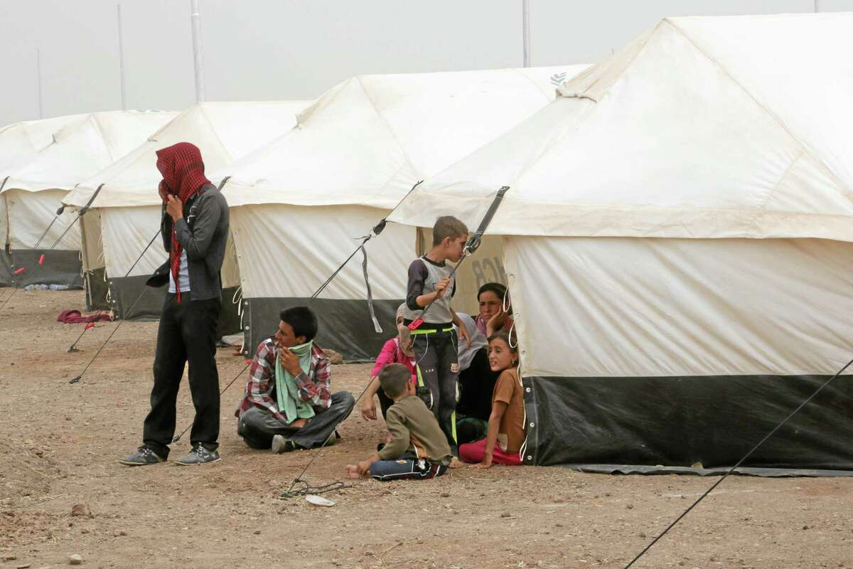 Displaced Iraqis settle at a new camp outside the Bajid Kandala camp in Feeshkhabour town, Iraq, Tuesday, Aug. 19, 2014. Some 1.5 million people have been displaced by fighting in Iraq since the Islamic State's rapid advance began in June, and thousands more have died. The scale of the humanitarian crisis prompted the U.N. to declare its highest level of emergency last week. (AP Photo/Khalid Mohammed)