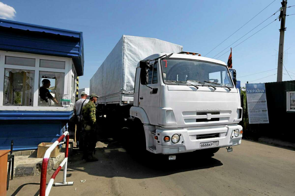 Ukrainian border guards look at the first truck as it passes the border post at Izvaryne, eastern Ukraine, Friday, Aug. 22, 2014. The first trucks in a Russian aid convoy crossed into eastern Ukraine on Friday, seemingly without Kiev's approval, after more than a week's delay amid suspicions the mission was being used as a cover for an invasion by Moscow. (AP Photo/Sergei Grits)