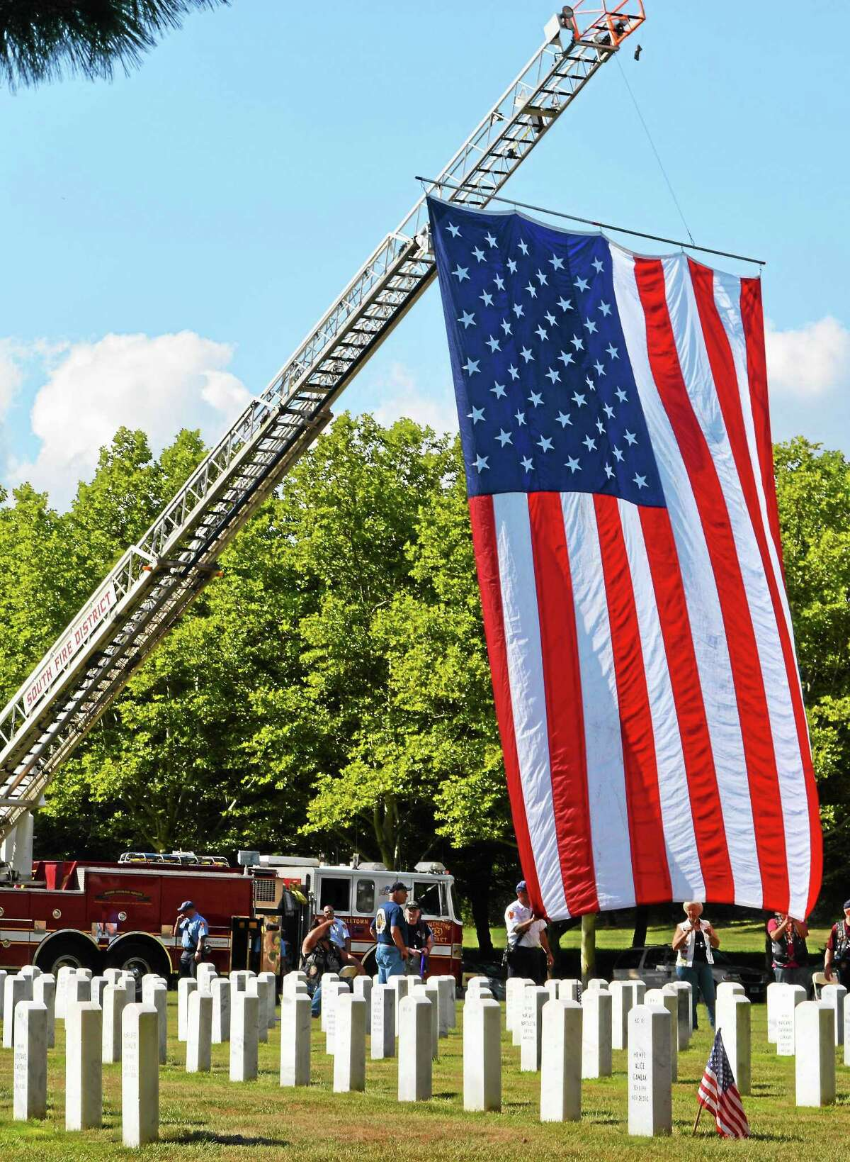 The city's South Fire District ladder truck raised a giant American flag to serve as a backdrop for the groundbreaking.