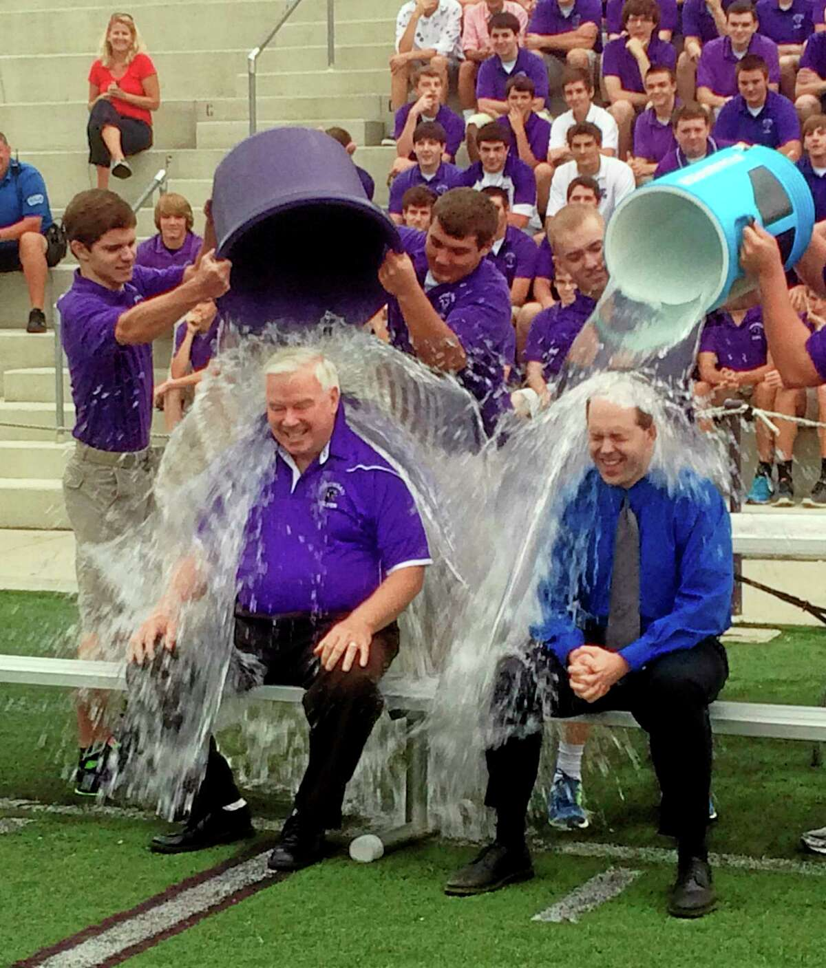 In this Thursday, Aug. 21, 2014, photo provided by the Archdiocese of Cincinnati, Jim Rigg, right, superintendent of the diocese's 113 schools, and Elder High School Principal Tom Otten take the ice-bucket challenge at Elder High School in Cincinnati. The archdiocese is discouraging its students and staff from donating any money raised as part of the challenge to the ALS Association, saying the group funds a study involving embryonic stem cell research