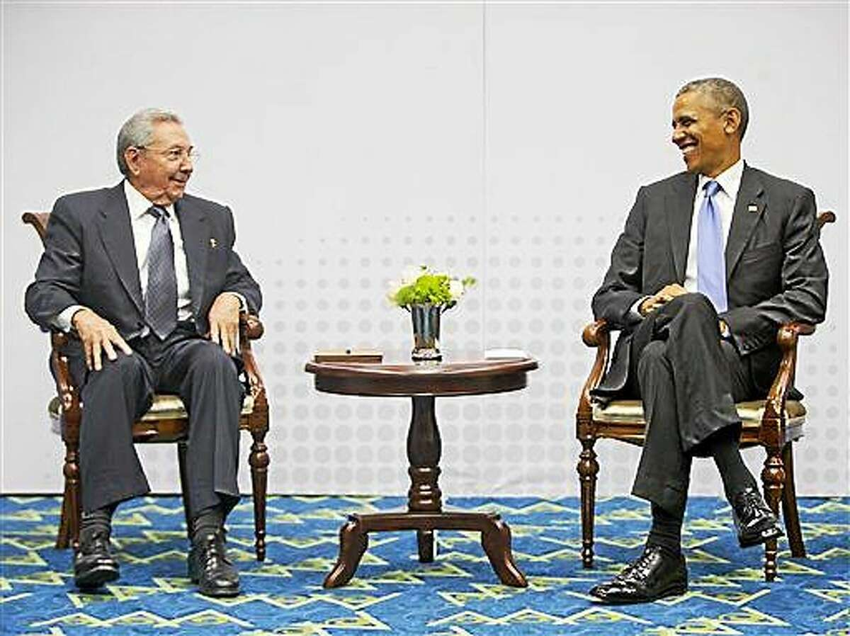 In this Saturday, April 11, 2015 photo, U.S. President Barack Obama, right, smiles as he looks over towards Cuban President Raul Castro, left, during their historic meeting, at the Summit of the Americas in Panama City, Panama. The leaders of the United States and Cuba held their first formal meeting in more than half a century on Saturday, clearing the way for a normalization of relations that had seemed unthinkable to both Cubans and Americans for generations.