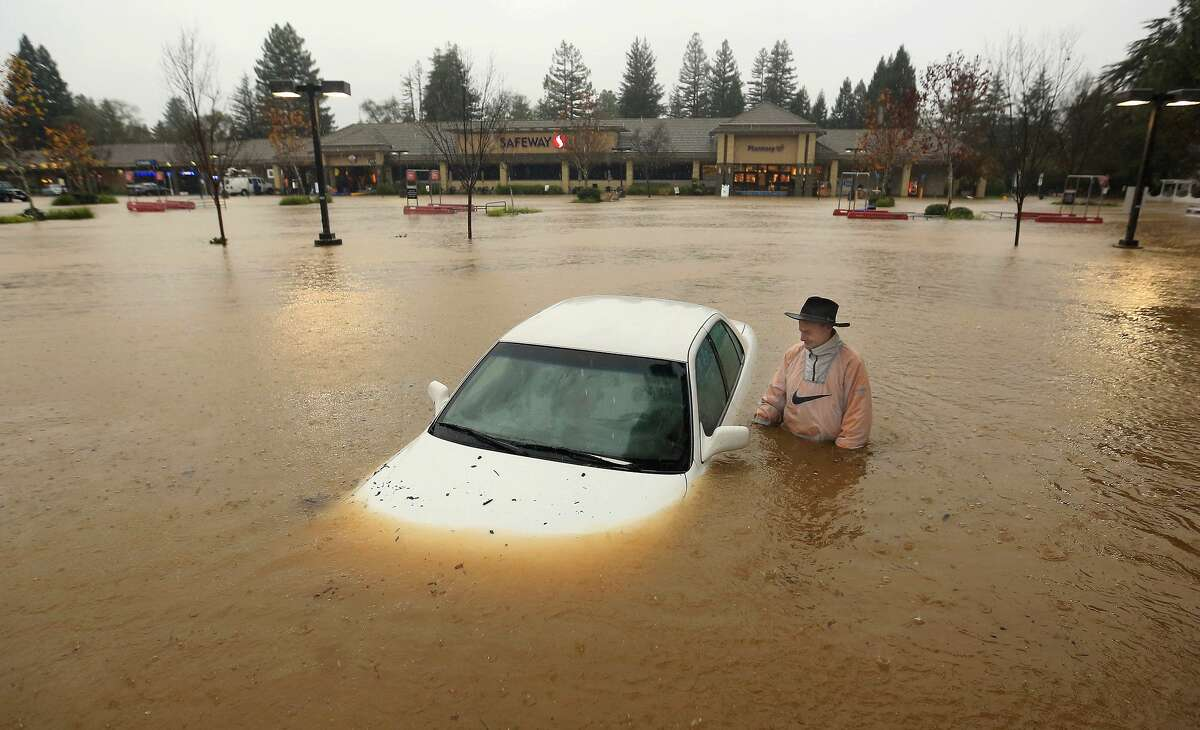 A resident of Guerneville, Calif., who parked his car overnight in the Safeway parking lot on Vine Street in Healdsburg, Calif., finds it nearly completely submerged as Foss Creek topped it's banks, Thursday morning, Dec. 11, 2014. A powerful storm churned down the West Coast Thursday, bringing strong gales and much-needed rain and snow that caused widespread blackouts in Northern California and whiteouts in the Sierra Nevada. Sonoma County authorities are recommending hundreds of people evacuate the lowest lying areas near the Russian River, which is projected to start overflowing overnight. (AP Photo, The Press Democrat, Kent Porter)