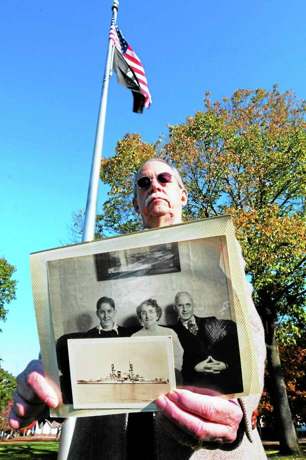 Tom Gray of Guilford holds a photo of the USS Oklahoma that was sunk at Pearl Harbor in 1941 and took the life of his cousin Edwin Hopkins, at left in the larger photo, as Hopkins sits with his mother and father. Photo: Peter Hvizdak — New Haven Register  / ©Peter Hvizdak /  New Haven Register