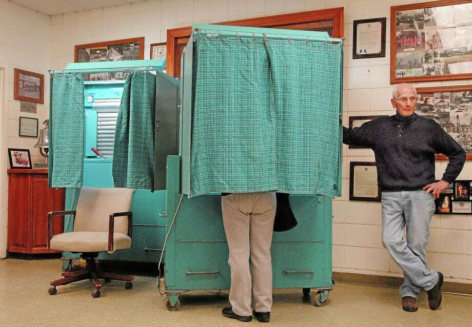 Machine tender Frank Augeri mans the voting booth in the South Fire District in Middletown in this file photo. Photo: Middletown Press File Photo