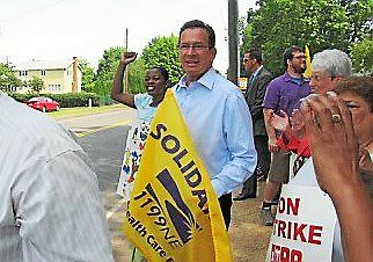 Gov. Dannel P. Malloy holds an SEIU 1199 flag on the picket line in 2012