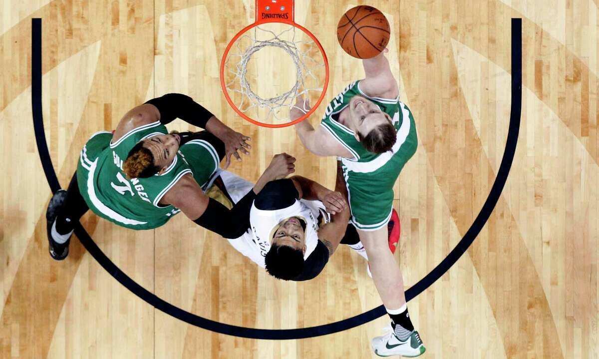 The Celtics' Kelly Olynyk drives to the basket against the Pelicans' Anthony Davis, center, with help from the Celtics' Jared Sullinger during Monday's game in New Orleans.