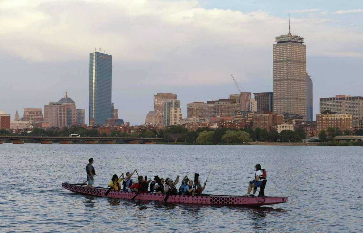 A boat glides along the Cambridge, Mass., side of the Charles River in front of the Boston skyline.