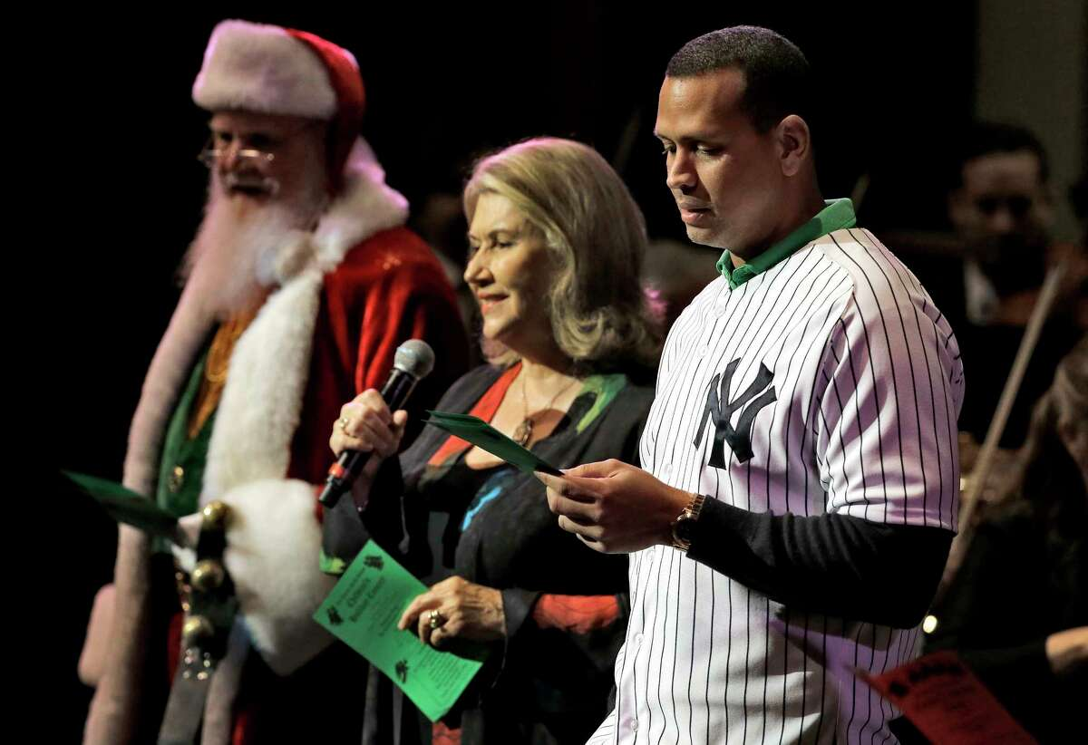 """The Yankees' Alex Rodriguez, right, is joined by Santa Claus and Mark K. Wilson as they sing Christmas carols to a group of Hillsborough and Pinellas County school children during the 27th annual Steinbrenner Family Children's Holiday Concert on Tuesday in St. Petersburg, Fla. Rodriguez also read """"Twas the Night Before Christmas"""" to the students."""