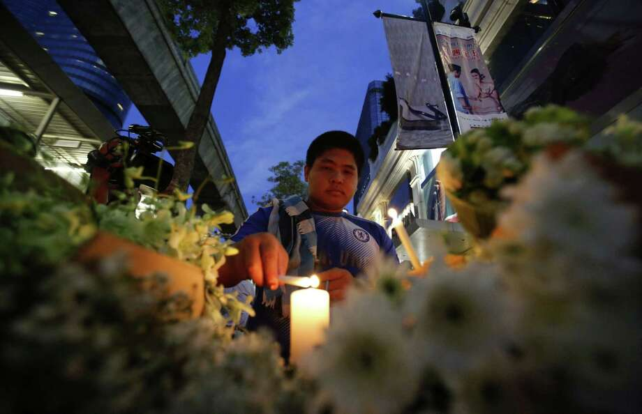 """A Thai lights a candle near the Erawan Shrine at Rajprasong intersection the day after an explosion in Bangkok, Thailand, Tuesday, Aug. 18, 2015. Thailand's Prime Minister Prayuth Chan-ocha called Monday's explosion at the busy intersection """"the worst incident that has ever happened in Thailand,"""" and promised to track down those responsible. Photo: AP Photo/Sakchai Lalit  / AP"""