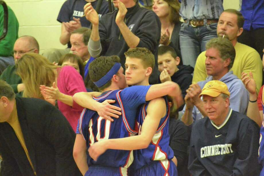 Coginchaug's Jack Granger hugs teammates Zach Vallone after Granger fouled out in the final minutes of a 51-41 loss to the Terryville. Photo: Pete Paguaga — Register Citizen