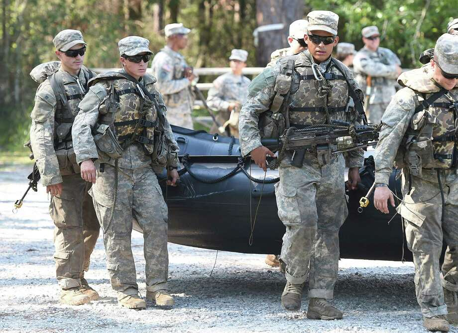 Army Rangers students carry a zodiac boat into the Yellow River on Tuesday, Aug. 4, 2015, at Camp James E. Rudder on Eglin Air Force Base, Fla. A female Ranger student is pictured (middle left).  Two out of 19 females have made it to the final phase of Army Ranger training which ends at Camp James E. Rudder on Eglin Air Force Base. Pentagon leaders decided in 2013 to investigate the possibility  of opening all military jobs to women. Photo: Nick Tomecek/Northwest Florida Daily News Via AP / Northwest Florida Daily News