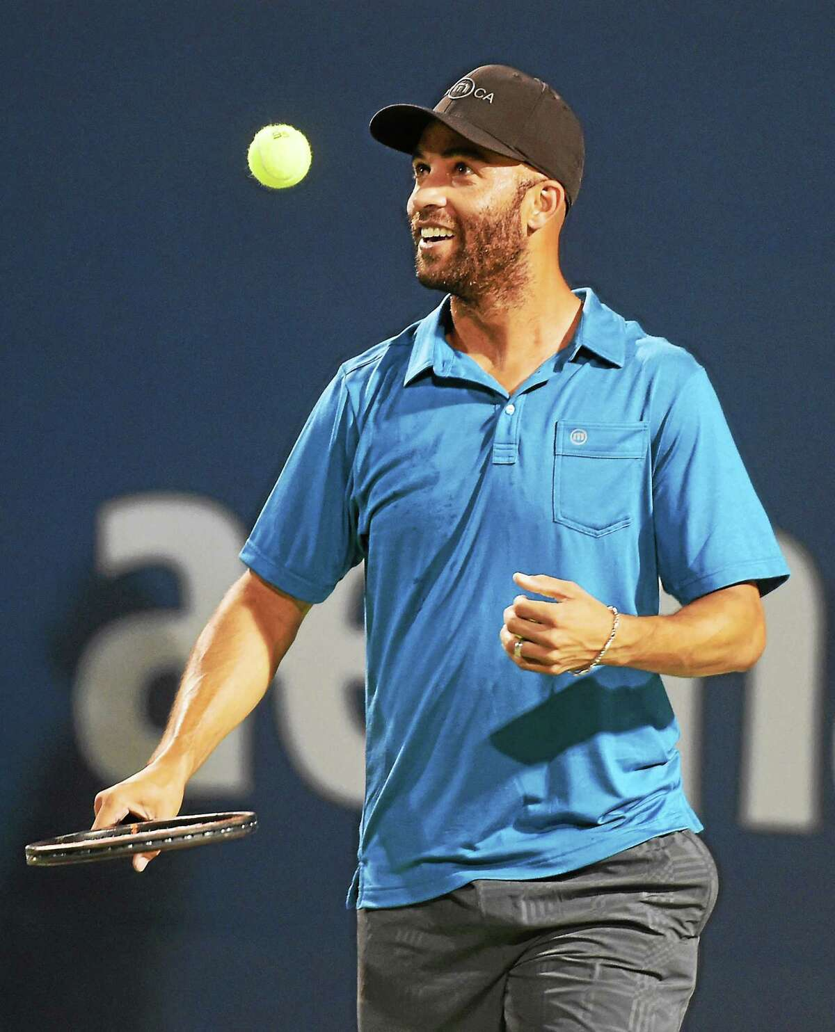 James Blake smiles after winning a point against Andy Roddick in the first set of an exhibition match on Thursday night at the Connecticut Tennis Center.