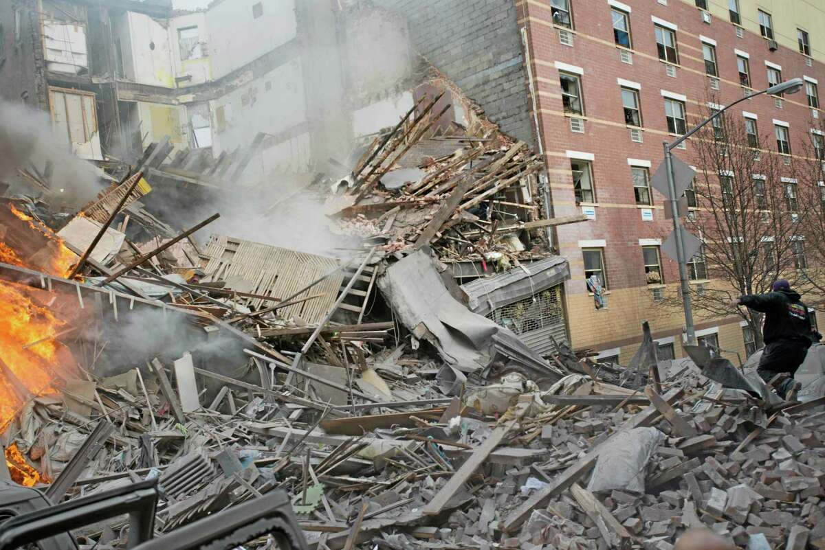 Emergency workers respond to the scene of an explosion and building collapse in the East Harlem neighborhood of New York, Wednesday, March 12, 2014. The explosion leveled an apartment building, and sent flames and billowing black smoke above the skyline. (AP Photo/Jeremy Sailing)