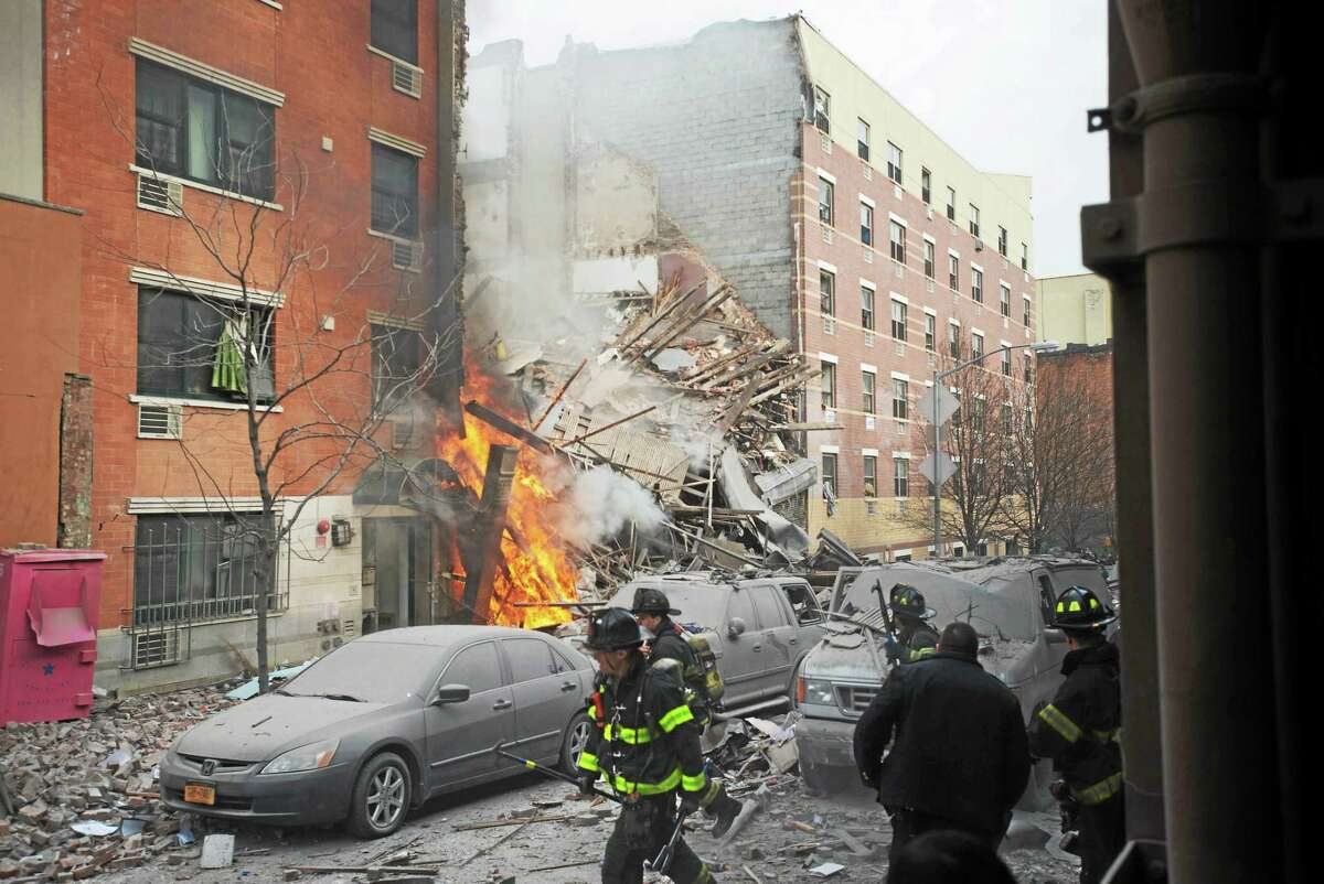 Firefighters work the scene of an explosion and building collapse in the East Harlem neighborhood of New York Wednesday. The explosion leveled two apartment buildings and sent flames and billowing black smoke above the skyline.