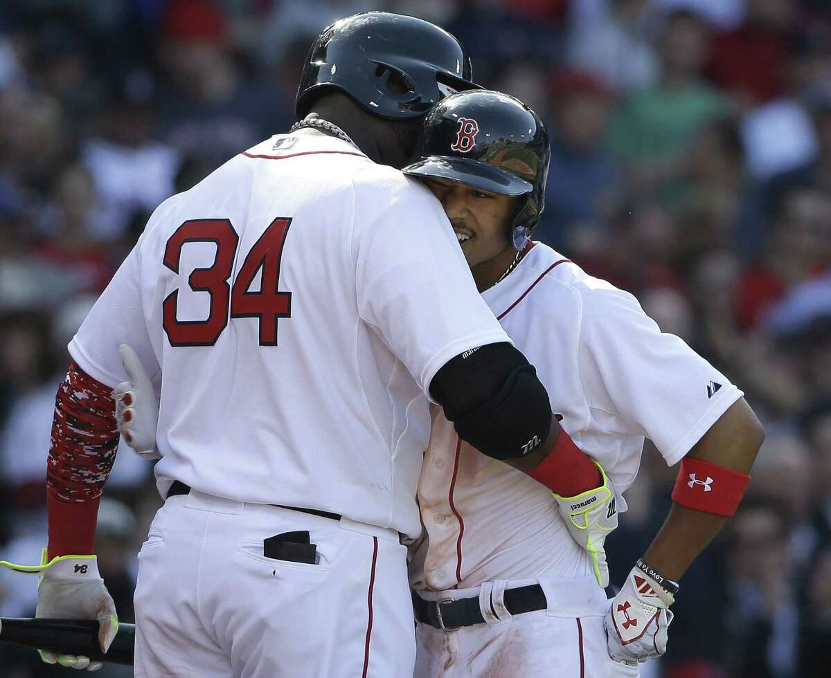David Ortiz, left, hugs Mookie Betts after Betts hit a three-run home run in the second inning Monday.