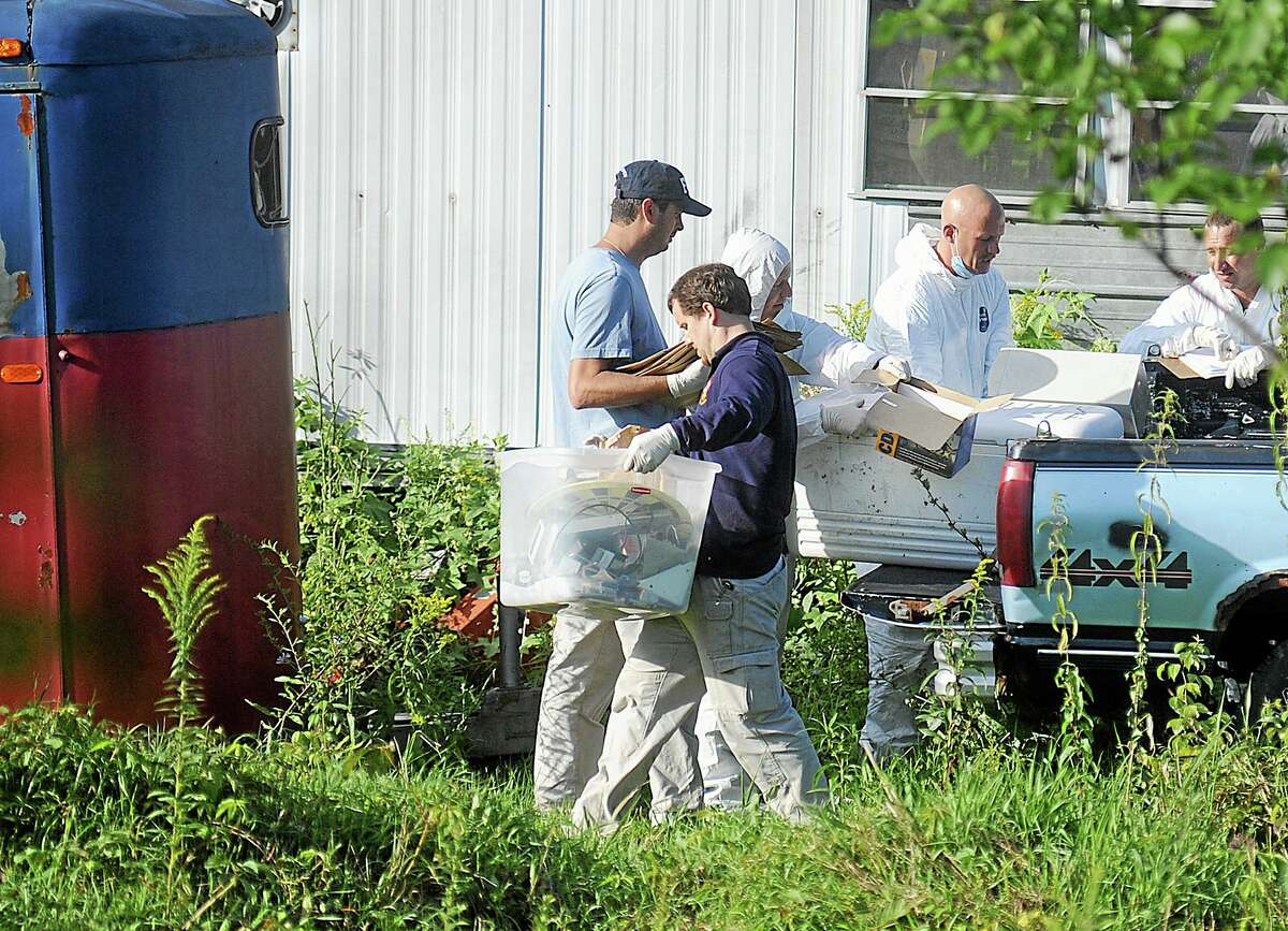 New York State Police crime scene investigators carry items from the bed of a pickup truck at the home of Stephen Howells II and Nicole F. Vaisey, in Hermon, N.Y., Sunday, Aug. 17, 2014. Vaisey and Howells were arrested Friday on charges of first-degree kidnapping with the intent to physically harm or sexually abuse two Amish sister. (AP Photo/Watertown Daily Times, Melanie Kimber Lago)