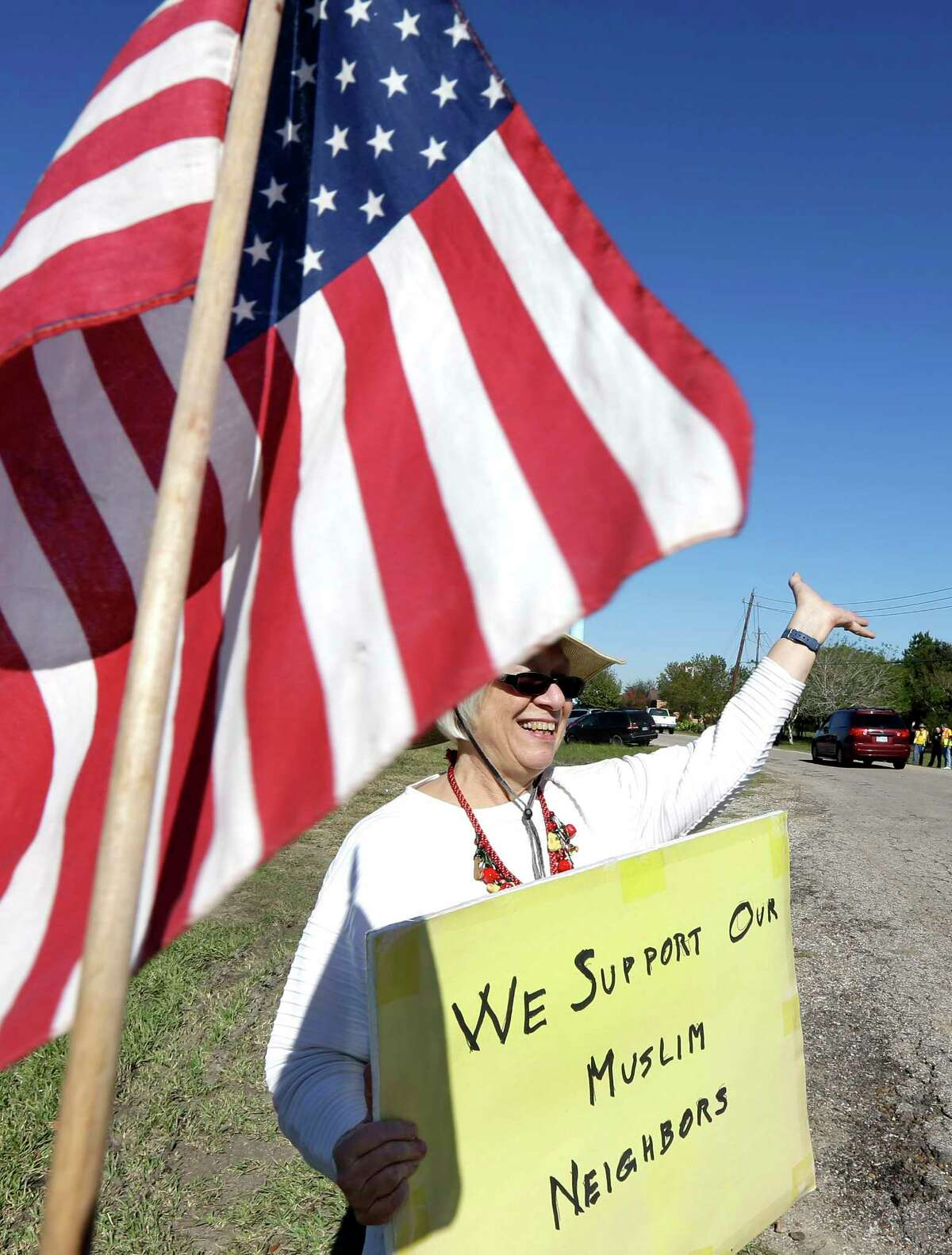 Jane Malin holds a sign as she waves to passing cars during a rally to show support for Muslim members of the community near the Clear Lake Islamic Center in Webster, Texas on Friday, Dec. 4, 2015. Members of several Unitarian Universalist churches and the Unitarian Voices for Justice group showed their support as attendees made their way to the center for Friday prayers. Organizers said the rally was scheduled prior to Wednesday's mass shooting in San Bernardino, Calif.