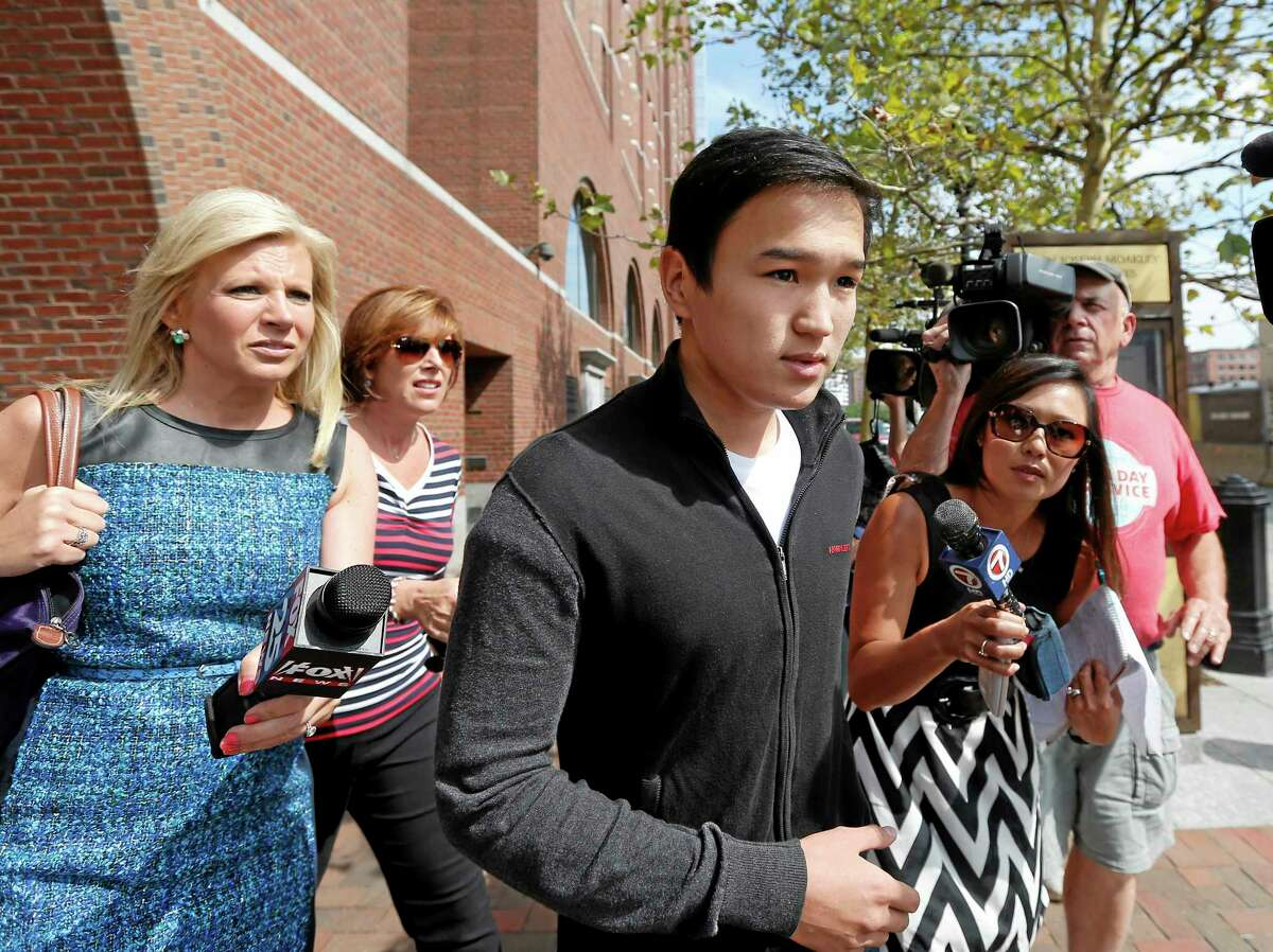 Ablaikhan Ismagulov, younger brother of Azamat Tazhayakov, is followed by media as he walks from federal court in Boston, Thursday, Aug. 21, 2014, where Dias Kadyrbayev, 20, a college friend of Boston Marathon bombing suspect Dzhokhar Tsarnaev, pleaded guilty to impeding the investigation into the deadly attack. Dias Kadyrbayev and Azamat Tazhayakov were both accused of removing a backpack containing emptied-out fireworks from Tsarnaev's dorm room after realizing he was suspected of carrying out the 2013 attack. (AP Photo/Elise Amendola)