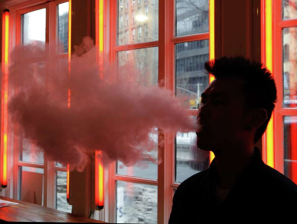 In this Feb. 20, 2014 photo, a man exhales vapor from an e-cigarette in New York.