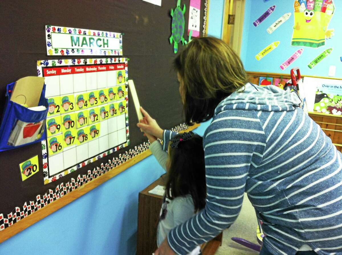 A parent participates in her daughter's developmental growth at nursery school as part of cooperative learning.