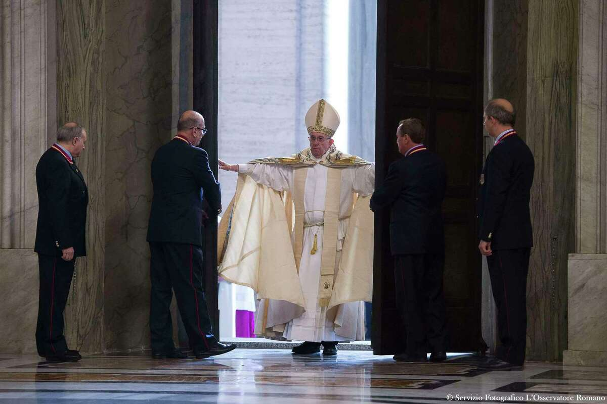 Pope Francis pushes open the Holy Door of St. Peter's Basilica, formally launching the Holy Year of Mercy, at the Vatican, Tuesday, Dec. 8, 2015. Francis stood in prayer on the threshold of the basilica's Holy Door then walked through it, the first of an estimated 10 million faithful who will pass through over the course of the next year in a rite of pilgrimage dating back centuries.