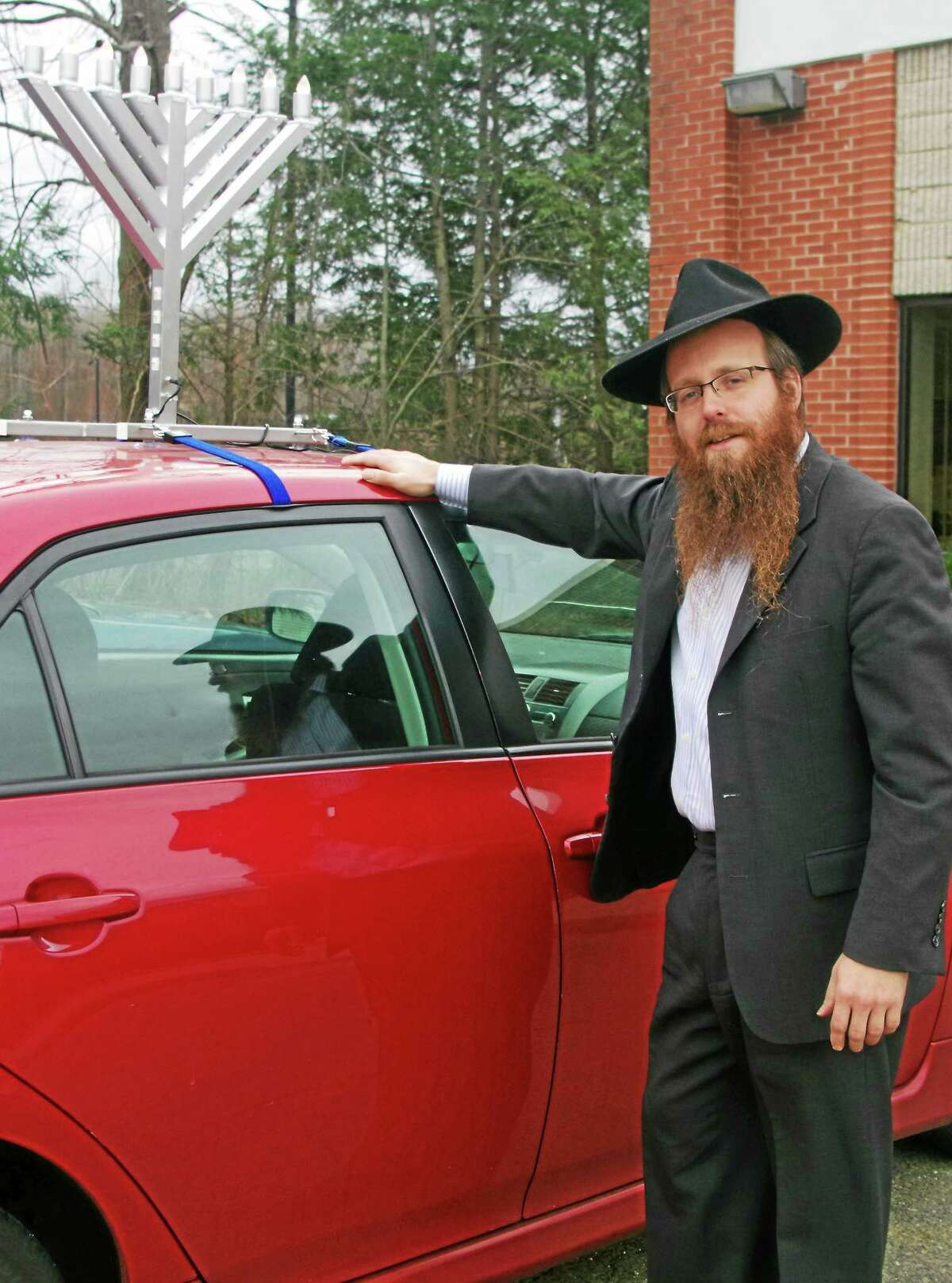 Rabbi Yosef Wolvovsky of the Benet Rothstein Chabad Jewish Center poses with the Menorah-mounted car he plans to ride in the upcoming parade on Monday.