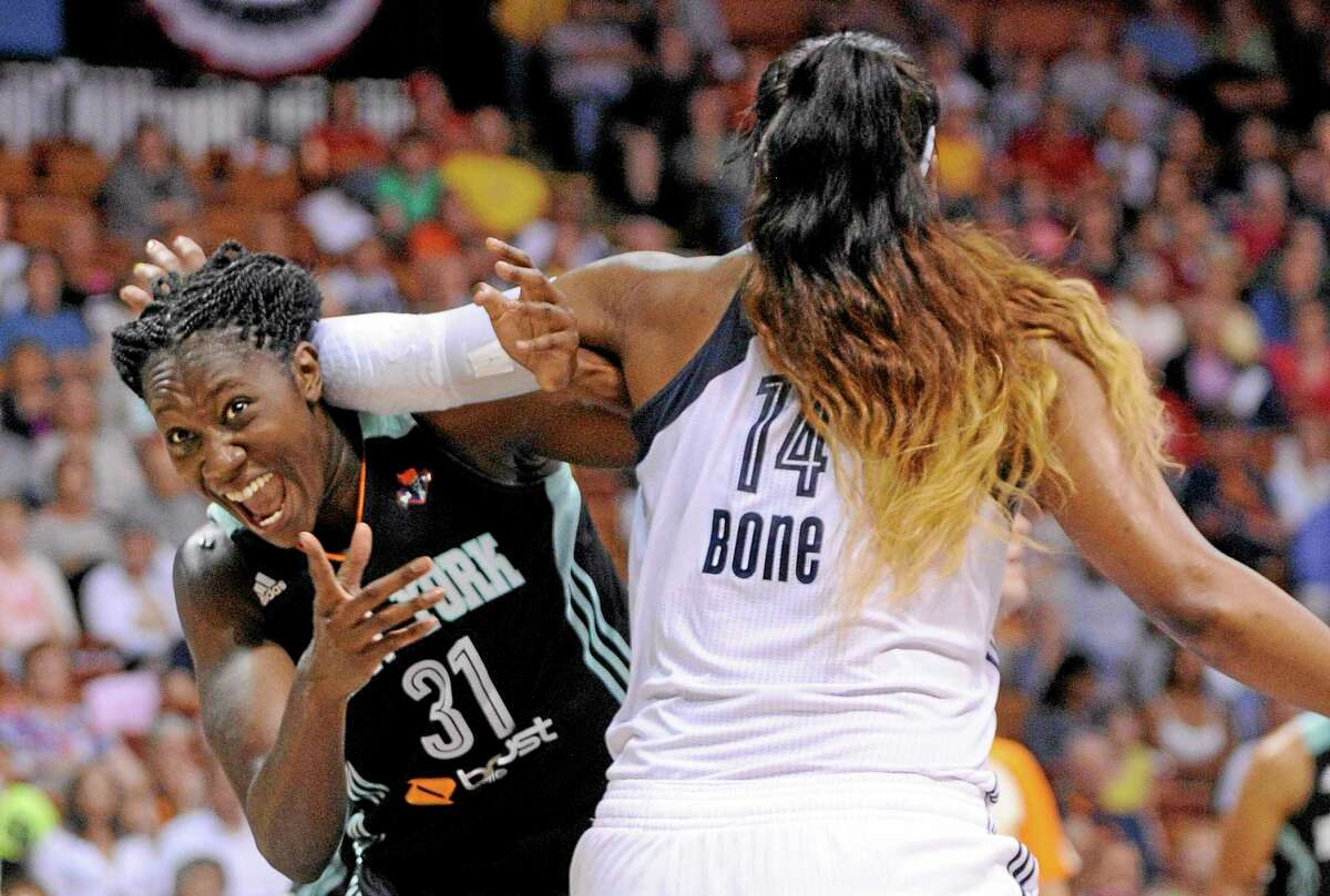 The New York Liberty's Tina Charles (31) looks for a foul call while being guarded by the Connecticut Sun's Kelsey Bone (14) during a June 15 game in Uncasville.