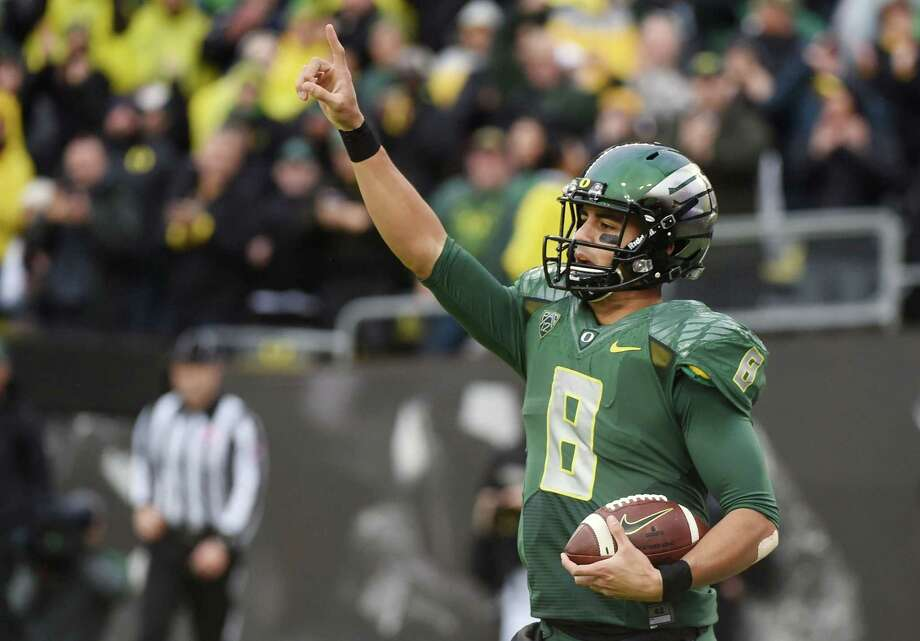 Oregon quarterback Marcus Mariota celebrates after scoring a touchdown during the first quarter of the Ducks' 44-10 win over Colorado on Nov. 22 in Eugene, Ore. Photo: Steve Dykes — The Associated Press File Photo  / FR155163 AP