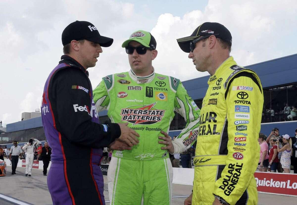 Denny Hamlin, left, talks with Kyle Busch, center, and Matt Kenseth after qualifying Friday at Michigan International Speedway in Brooklyn, Mich.