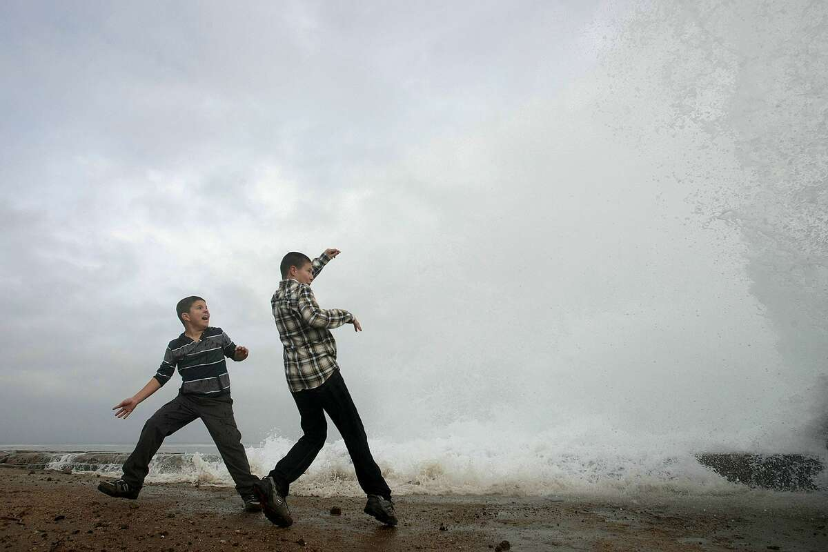 Aidan Stephenson, 12, and Conor Stephenson, 10, visiting from Phoenix, watch the waves breaking on the rocks on Ocean View Blvd. on Dec.10, 2014, in Pacific Grove, Calif. The National Weather Service issued a high wind and flash flood warning. The storm is expected to arrive Wednesday and pelt the region through Thursday.