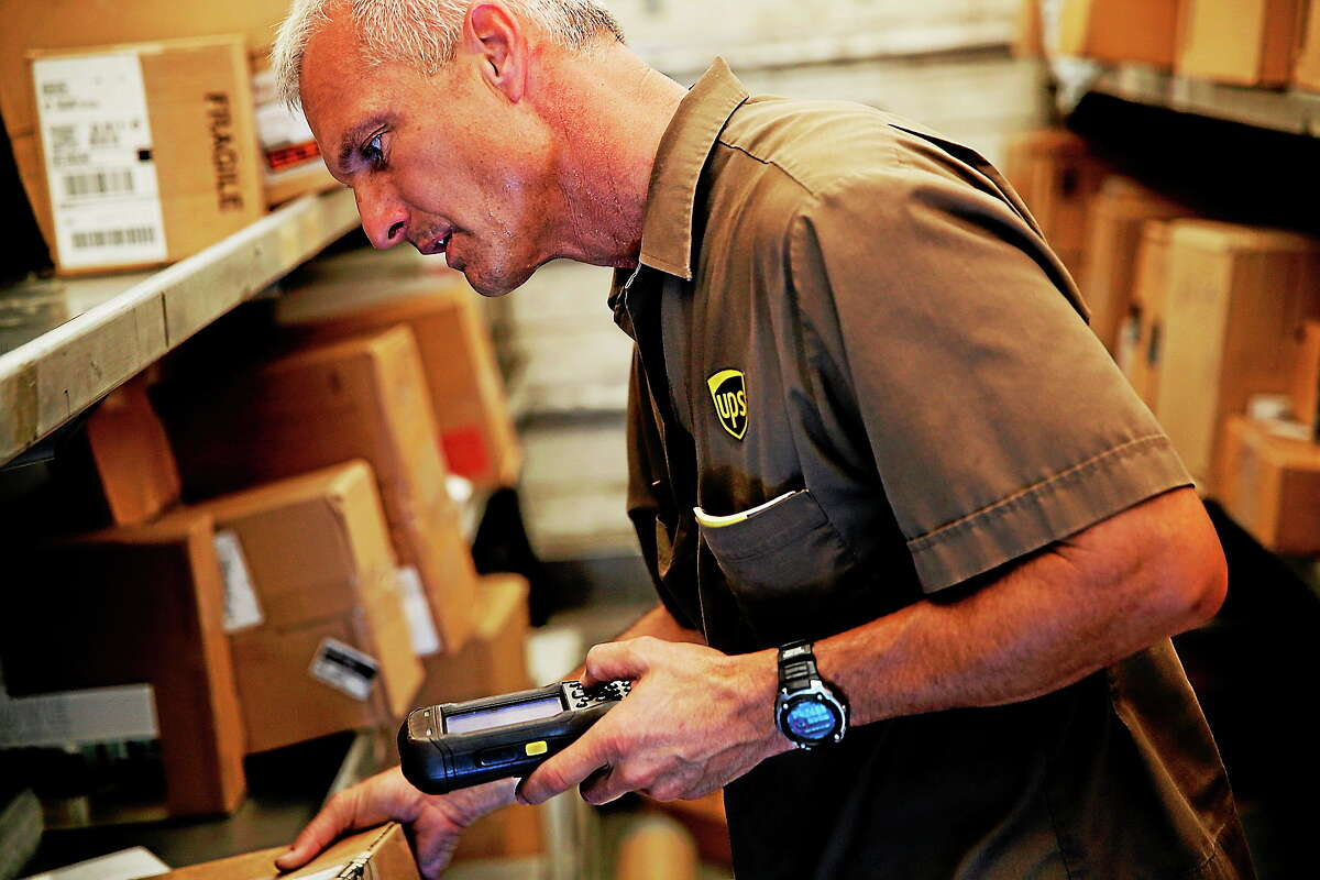 In this June 20, 2014 photo, United Parcel Service driver Marty Thompson scans a package before a delivery.